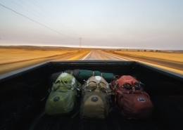Three backpacks in the bed of a pickup truck